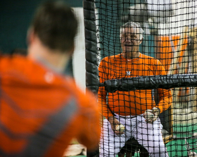 Hitting Coach Leon Roberts sits behind the screen in the indoor cage tossing flips (photo by James Ramirez)
